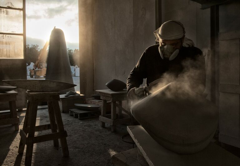 artist amidst dust and sunlight while he carves a stone sculpture