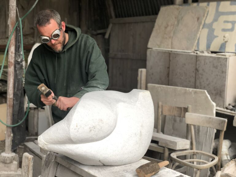 Artist carving stone with hand tools