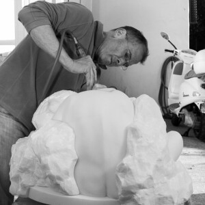 Jim Hager carving a figure in white marble